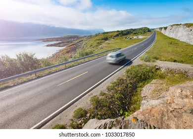 Car in mountains of Norway, Europe. Auto travel through scandinavia. Blue cloudy sky and lake in background.