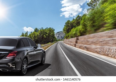 Car moves on a mountain road on a summer sunny day.