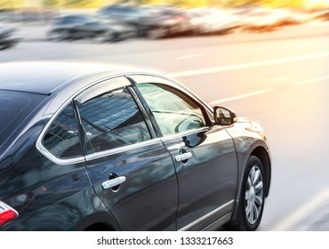 Car moves on a multi-lane road. On the opposite side of the road several cars are parked.