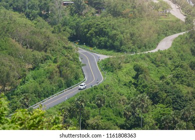 A car moving downhill from the Promthep Cape Viewpoint as seen from Windmill Viewpoint, Phuket, Thailand