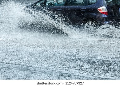 car moving with high speed through water puddle on flooded city road during heavy rain