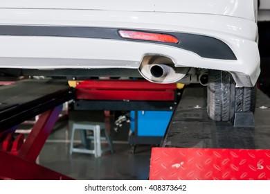 Car muffler in process of being modified in garage