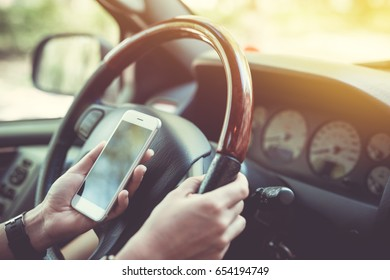 Car navigator. Woman holding the phone while driving