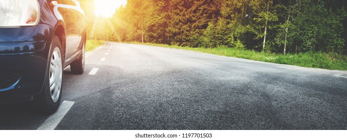 Car on asphalt road on summer day at park. Transportation panoramic background with sunlight