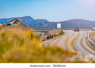 Car on Atlantic road in Norway, Europe. Auto travel through scandinavia. Blue sky in background.