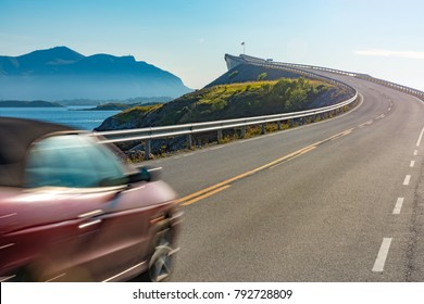 Car on Atlantic road in Norway, Europe. Auto travel through scandinavia. Blue sky and water in background