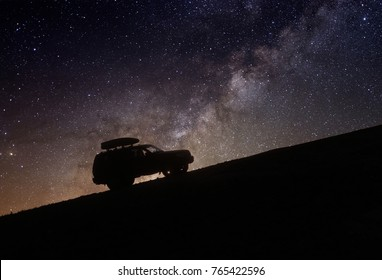 The car on a background of stars rides on top of the mountain at night