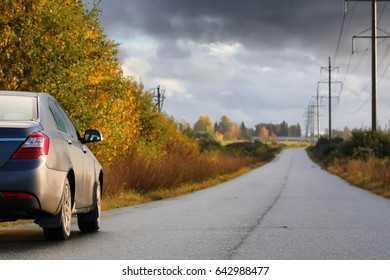 car on country road lane in rainy autumn day