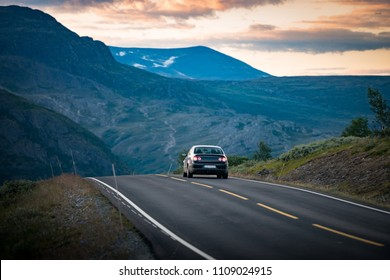 Car on country road in Norway, Europe, Scandinavia. Auto travel on sunset. Orange sky with clouds.