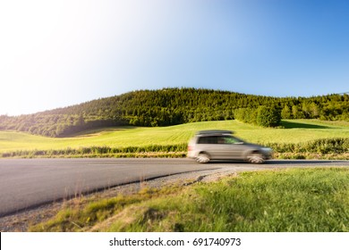Car on country road in Norway, Europe, Scandinavia. Auto travel on sunny day. Blue sky with no clouds.