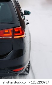Car on country road in winter day. Closeup of a taillight on a modern car