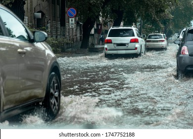 Вriving car on flooded road during flood caused by torrential rains. Cars float on water, flooding streets. Splash on car. Flooded city road with large puddle.  Flooding after heavy rains at city