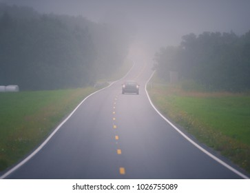 Car on foggy road in Norway, Europe. Auto travel through Scandinavia. Dangerous driving conditions.