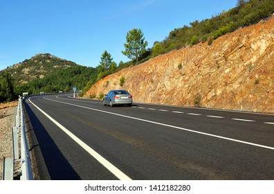 Car on the highway in the mountain pass Puerto de Niefla. Natural Park of the Valley of Alcudia and Sierra Madrona, province of Ciudad Real, Spain