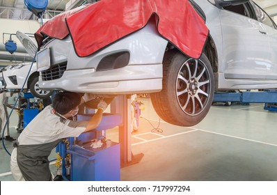 Car on lift to repair suspension in the garage with mechanic working under lifted car to change motor oil and maintenance repair at service station
