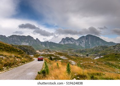 A car on the road in Durmitor national park, Montenegro. View of Prutas mountain