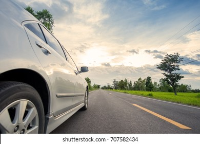 Car on road with meadow and sunset sky for travel