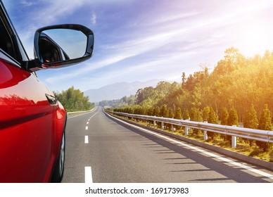 Auto auf der Straße mit unscharfem Bewegungshintergrund.