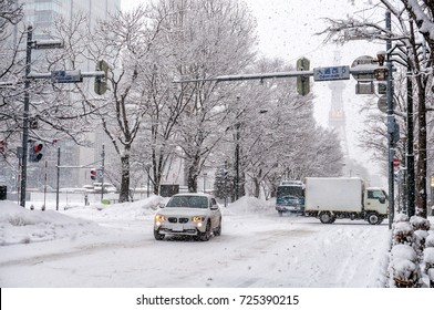 Car on road near Odori Park and background of Sapporo TV Tower in winter season at Sapporo, snowy day, Hokkaido, Japan.