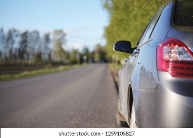 The car is on the road. Summer road on which there is a parked car. Travelling by car