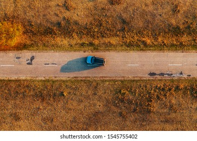 Car on the road through autumn countryside, aerial view directly above from drone pov