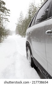Car on a snowy forest road, side view