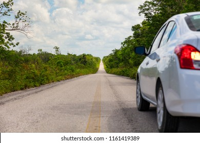 Car on straight empty Mexican road on the Yucatan Peninsula