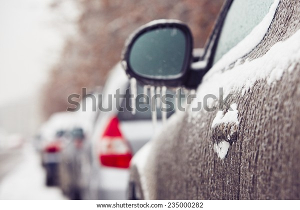 Car on the street covered by icy rain