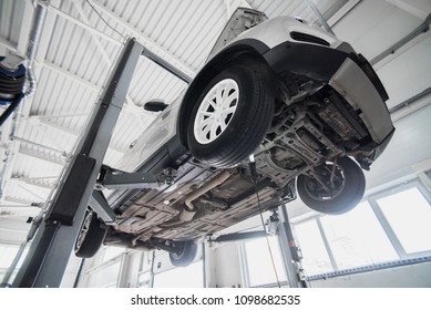 Car on a wheel alignment lift in auto service. Diagnosis of the chassis of the car raised at the elevator.