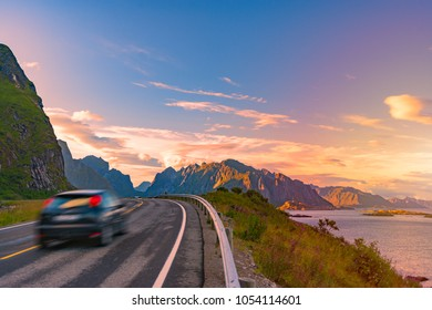 Car on winding country road in Norway, Europe, Scandinavia. Auto travel on sunset. Blue sky with clouds and mountains. Lofoten islands.