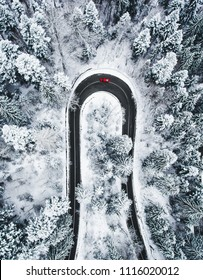 Car on winding winter road as seen from above