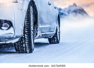 Car on winter frozen road.  Winter car tires on snow.
