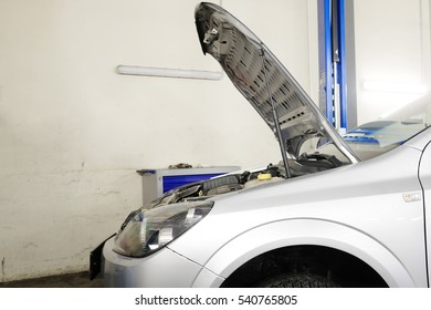 Car with an open hood in a repair station