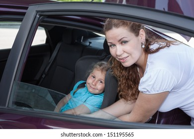 Car opened door with helping mother to fast small child for journey