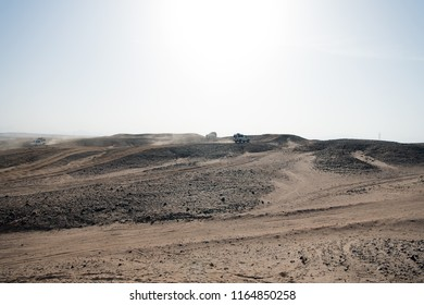 Car overcome sand dunes obstacles. Competition racing challenge desert. Car drives offroad with clouds of dust. Offroad vehicle racing obstacles in wilderness. Endless wilderness. Race in sand desert.