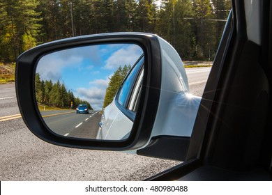 Car overtaking another vehicle on the highway in Finland. Auto photographed through a mirror.