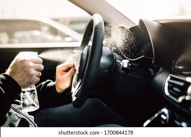 Car owner disinfecting vehicle with alcohol based sanitizing solution spray.Touched surfaces sanitation.Coronavirus COVID-19 spread prevention.Cross-contamination.Steering wheel disinfection