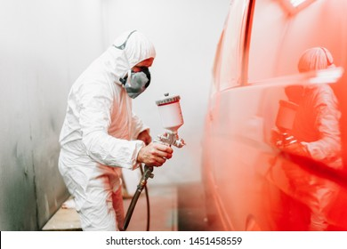 car painter engineer and auto mechanic working and painting a red car using spray gun and compressor