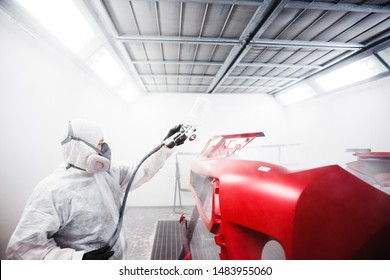 Car painter sprays varnish in paint booth.