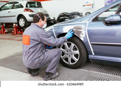Car painting procedure at auto service store. Selective focus on worker's hand.
