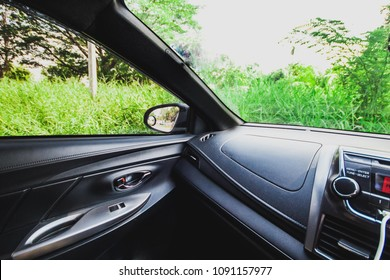 The car is parked in the forest outside the grass and green leaf beautiful nature.