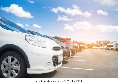 Car parked in large asphalt parking lot in a row with beautiful sky background. Outdoor parking lot with nature fresh ozone and green environment of travel transportation business concept