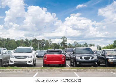 Car parked in large asphalt parking lot with trees, white cloud, blue sky background. Outdoor parking lot with fresh ozone and green environment of travel transportation concept