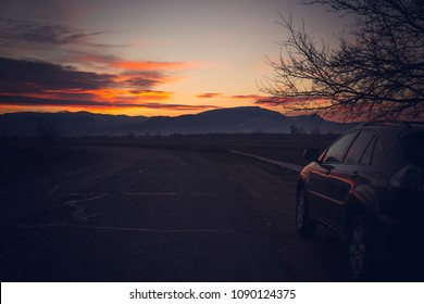 Car parked in the nature with beautiful sunrise view. Concept of roadtrip, exploration and outdoor activity.