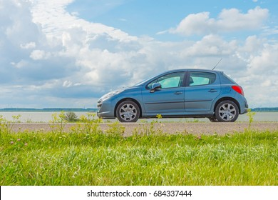 Car parked on a dike along a lake in summer