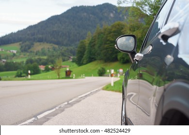 Car parked on the roadside in front of mountain and alpine valley. Travel concept