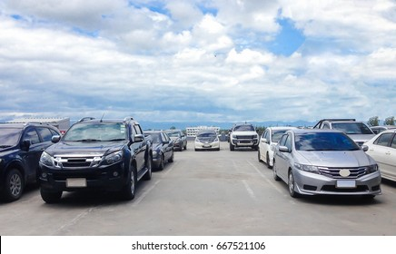 Car parked in parking lot and empty space at the rooftop of car parking building with white cloud and blue sky background