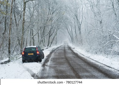 car parked with red lights in the border of a road in the forest under the snow, Rotterdam, Netherlands