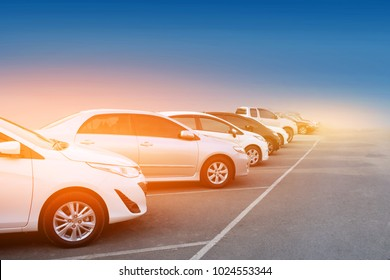 Car parked row on road,Car a lot parking in line and sunset,Transportation and technology concept