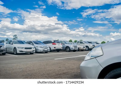 Car parking in large asphalt parking lot with beautiful sky background. Outdoor parking lot with nature fresh ozone and green environment of travel transportation business concept